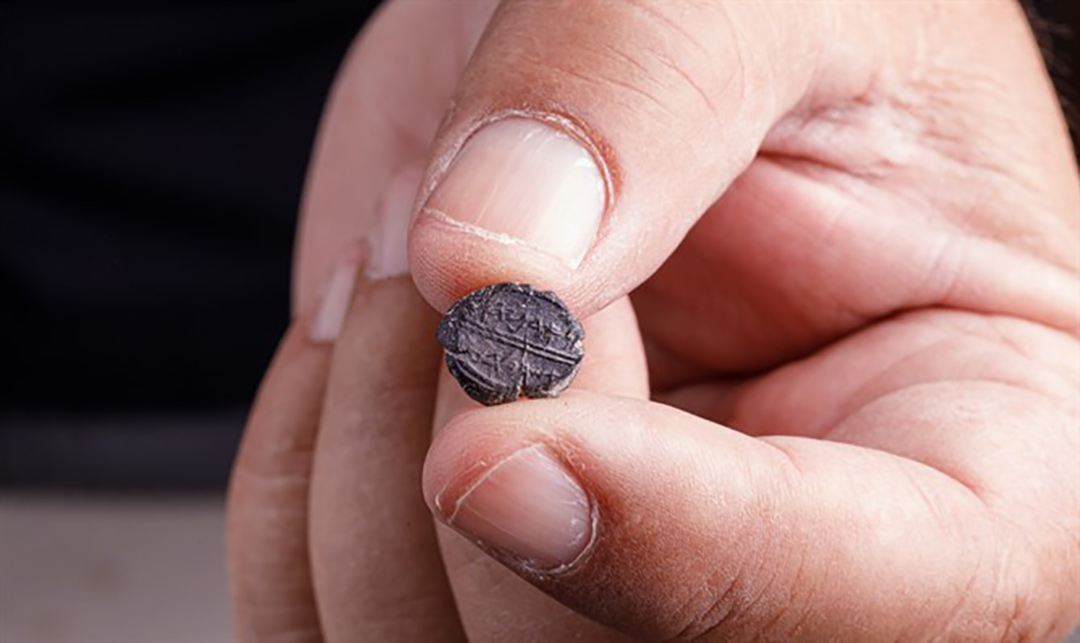 Archeologist holding the Adonijah seal recently excavated near the Western Wall in Jerusalem