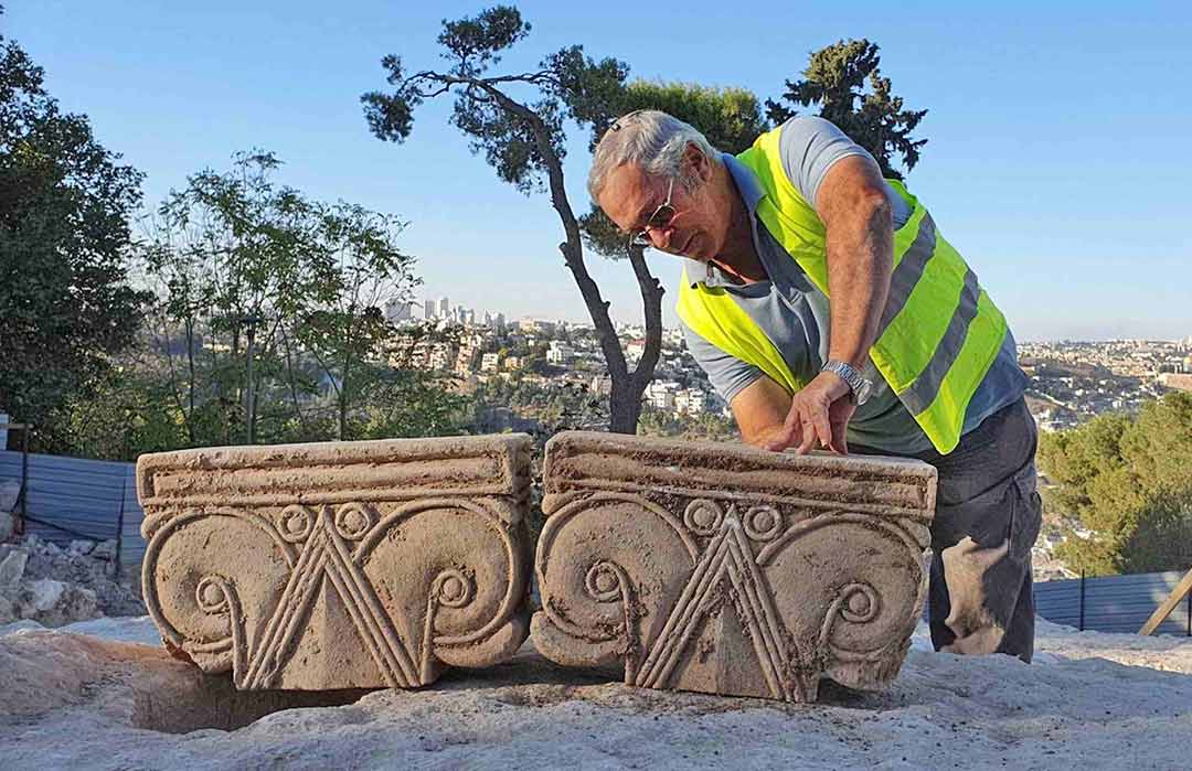Director Yaakov Billig with two proto-Aeolic capitals at the Armon HaNatziv excavation site in Israel