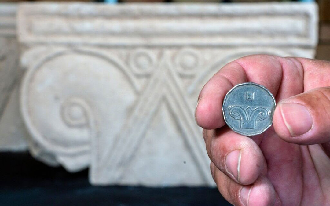 Holding a modern five-shekel coin
