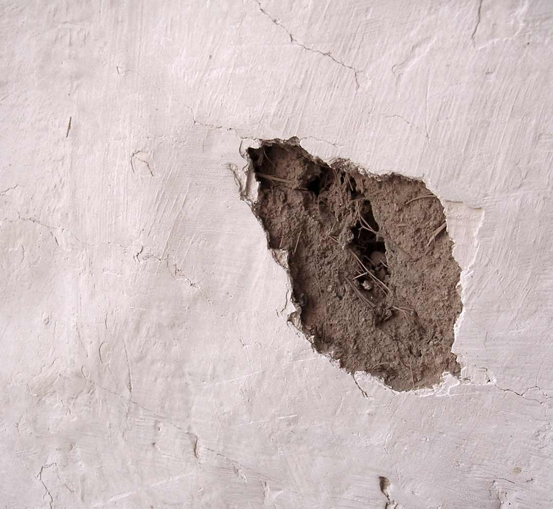 Layers of plaster chipped off reveal  wall material