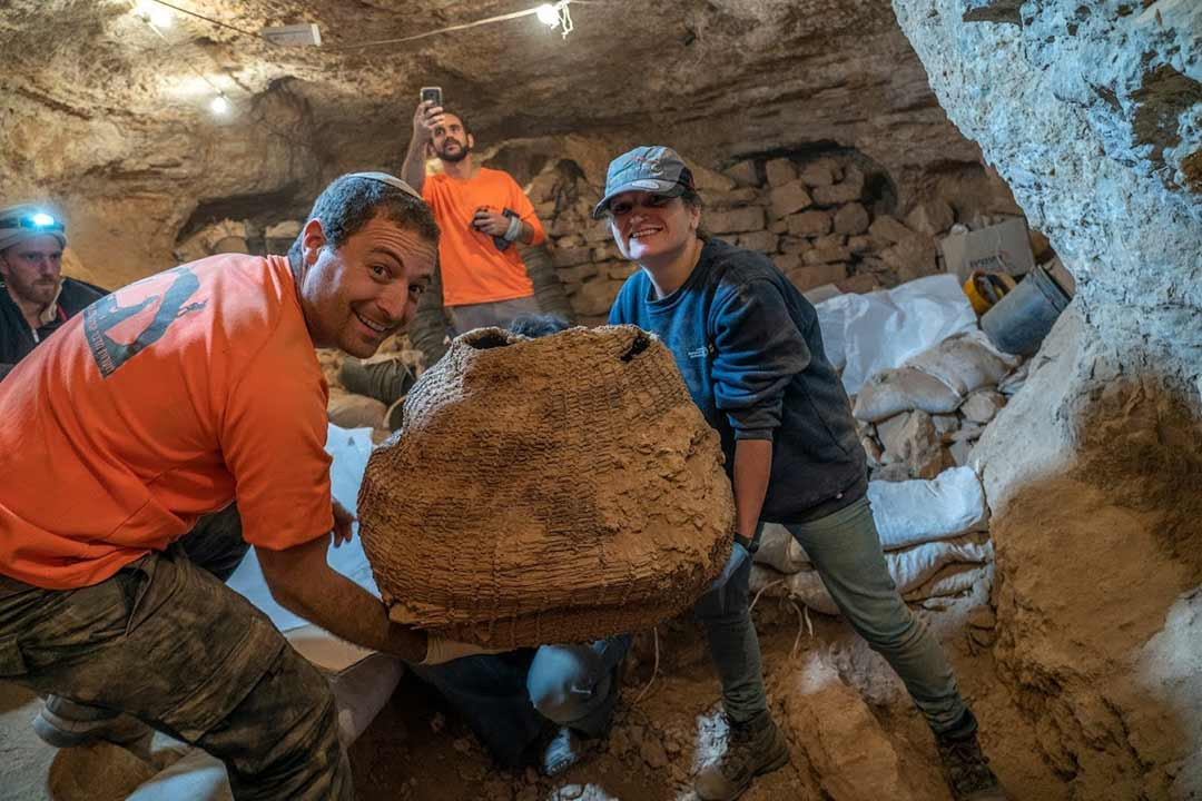 Archaeologists holding what may be the world's oldest surviving woven basket