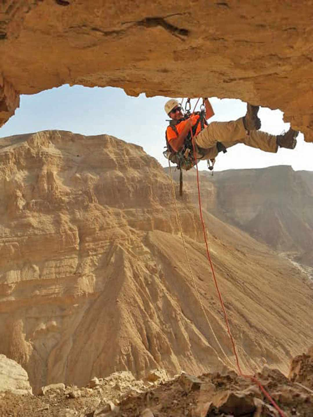 Archaeologist rappelling to explore the caves